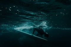 Man holding a surf board dive under the wave. Man holding a white surf board dive under the wave on the clear blue sea water ready to surfing royalty free stock photography