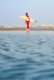 Man holding a surfboard on the beach. With calm seaside Royalty Free Stock Photography