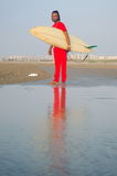 Man holding a surfboard on the beach. With calm seaside Stock Images