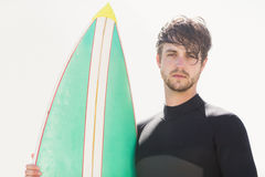 Man holding surfboard on the beach Stock Photography