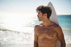 Man holding surfboard on beach. Young man holding surfboard on beach stock photo