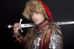 Man holding a sword and posing Stock Images