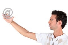 Man holding the at symbol Stock Image