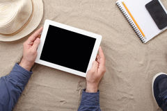 Man holding tablet with blank screen lying on the beach Stock Image