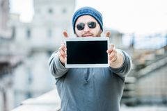 Man holding a tablet with both hands - urban blurred background Royalty Free Stock Photography
