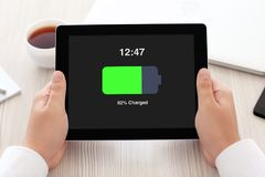 Man holding tablet with charged battery on screen in office Royalty Free Stock Images