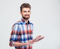 Man holding tablet computer and looking at camera. Portrait of a smiling man holding tablet computer and looking at camera isolated on a white background Stock Images