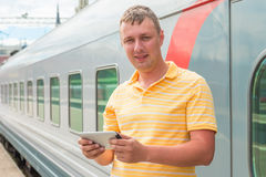 Man holding a tablet computer near the train Stock Photography