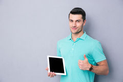 Man holding tablet computer and showing thumb up. Happy young man holding tablet computer and showing thumb up over gray background Royalty Free Stock Photos