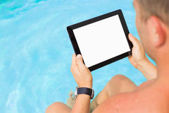 Man holding tablet computer by the swimming pool Stock Image