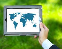 Man holding tablet computer with world map Stock Photo