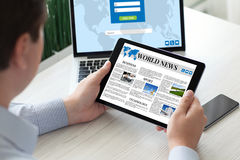 Man holding tablet computer world news with notebook phone Royalty Free Stock Photos