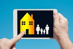 Man holding a tablet device showing family housing concept royalty free stock photo