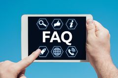 Man holding a tablet device showing frequently asked questions i. Cons FAQ and touching the screen with a finger with blue sky in background royalty free stock image