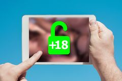 Man holding a tablet device showing lock icon allowing permission to people over 18 to watch adult content. Touching the screen with a finger with blue sky in stock images