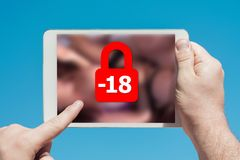 Man holding a tablet device showing lock icon denying permission. To people under 18 to watch adult content, touching the screen with a finger with blue sky in Stock Photography