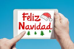 Man holding a tablet device with text in Spanish `Feliz Navidad Merry Christmas and touching the screen. With a finger with blue sky in background Royalty Free Stock Images
