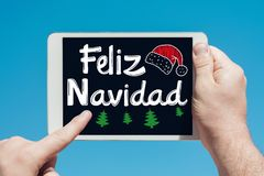 Man holding a tablet device with text in Spanish `Feliz Navidad Merry Christmas and touching the screen. With a finger with blue sky in background Stock Photo