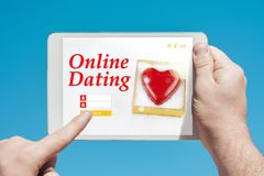 Man holding a tablet device visiting an online dating website lo. Oking for friendship or sex and touching the screen with a finger with blue sky in background stock images