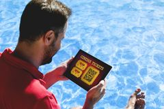Man holding a tablet with electronic cinema tickets in the screen, while sitting on the poolside. Online cinema tickets in a tablet screen ready to print Stock Images