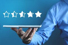 Man holding tablet. Five stars. Increase rating royalty free stock image