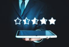 Man holding tablet. Five stars. Increase rating royalty free stock photography