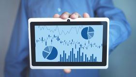 Man holding tablet with graphs in screen stock photos