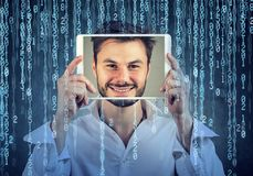 Man holding tablet with his face displayed on a screen on binary code background. Happy man holding tablet with his face displayed on a screen isolated on binary stock photos