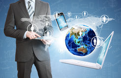 Man holding tablet. Near the earth and electronics Royalty Free Stock Image