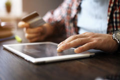 Man holding tablet pc and credit card indoor Stock Photography