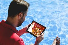 Man holding a tablet with pizza shop website in the screen, while sitting on the poolside. Stock Images