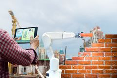 Man holding a tablet Remote control Smart robot industry 4. 0 arm brick building construction human force. Remote wifi stock photography