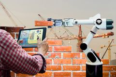Man holding a tablet Remote control Smart robot industry 4.0 arm brick building construction. Human force remote wifi royalty free stock images