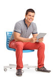 Man holding a tablet seated on a chair Stock Photo