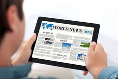 Man holding tablet with world news site on a screen Stock Images