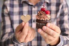 Man holding tasty cupcake and wooden heart Stock Image