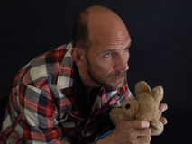 Man Holding a Teddy Bear. A man looking to the sky while holding a teddy bear isolated by a black back ground Royalty Free Stock Photos