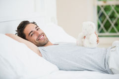 Man holding teddy bear while relaxing on bed Royalty Free Stock Image