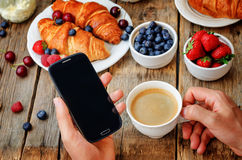 Man holding telephone and cup of coffee Royalty Free Stock Photo