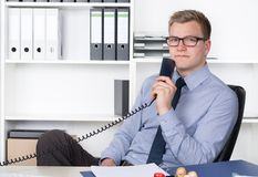 Man is holding a telephone receiver in the office Stock Photography