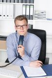 Man is holding a telephone receiver and a pen Royalty Free Stock Image