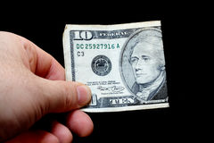 Man holding a ten dollar bill. Isolated on black background royalty free stock photography