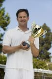 Man Holding Tennis Trophy net on tennis court Stock Photo