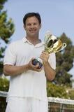 Man Holding Tennis Trophy net on tennis court portrait Stock Images