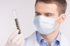 Man holding test tube and wearing mask. Stock Photos