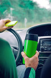 Man holding thermo mug and smartphone. Close up of male`s hands holding thermo mug and smartphone driving a car Royalty Free Stock Photos