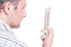 Man holding thermometer and checking temperature Royalty Free Stock Photo