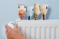 Man holding thermostat with banknotes Stock Photo