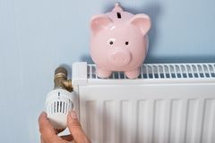 Man holding thermostat with piggy bank on radiator Stock Images