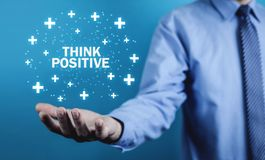 Man holding Think Positive words with plus signs. stock images